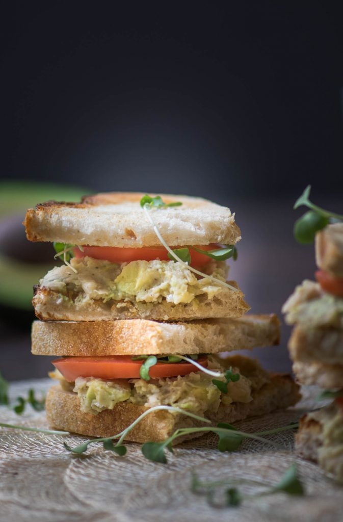 Healthy avocado and white bean sandwich halves stacked with a dark background