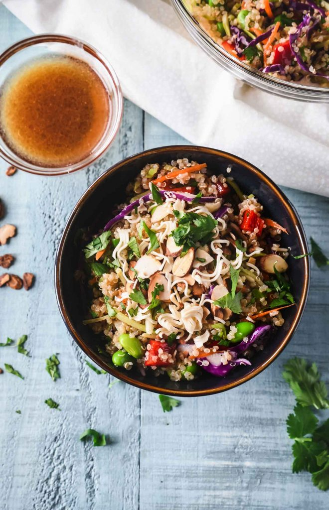 Asian quinoa salad in a dark blue bowl on a light blue background