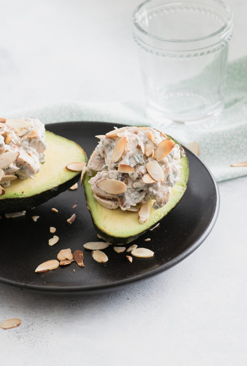 Avocados stuffed with chicken salad on a black plate
