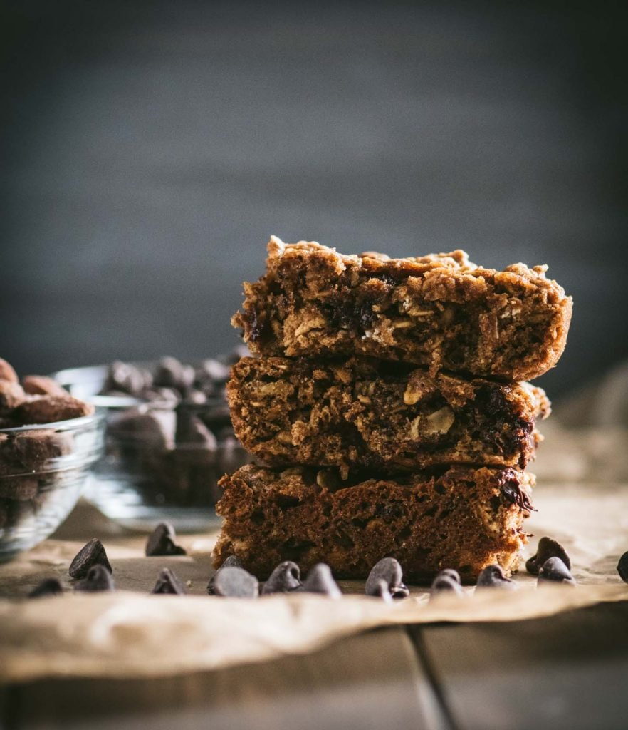 Three chocolate chip oatmeal bars stacked on a piece of parchment paper