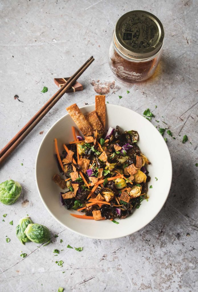Crispy brussels sprouts topped with wonton strips in a cream bowl