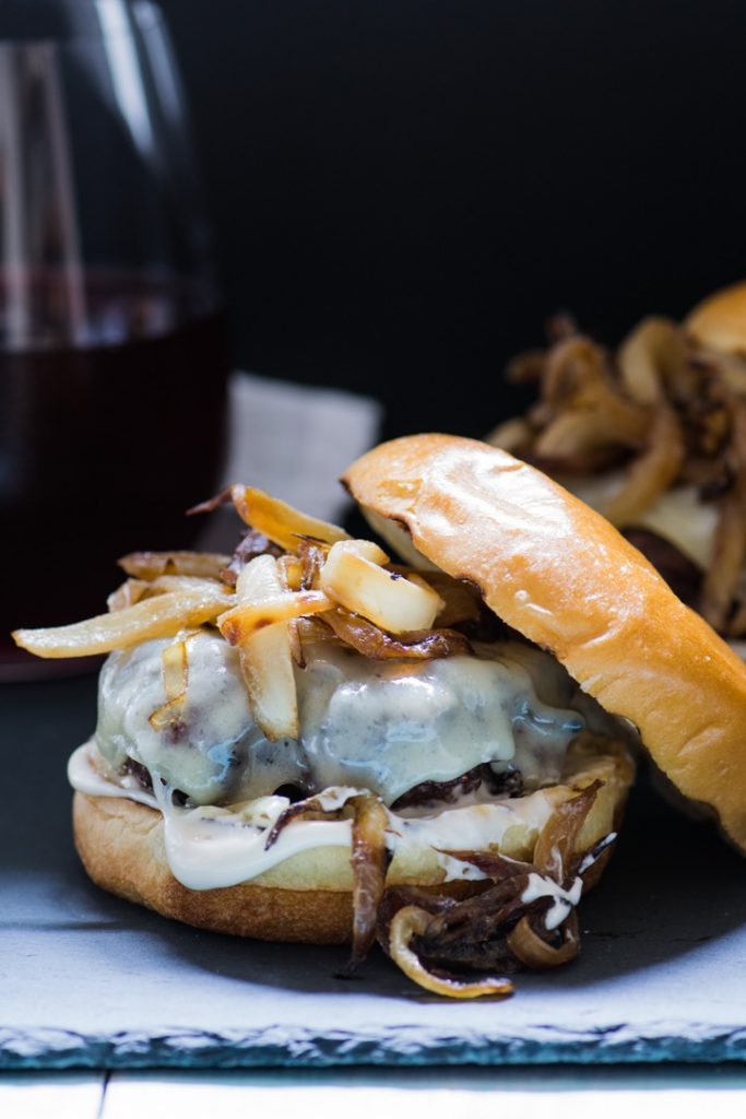 Dark + moody burger topped with caramelized onions