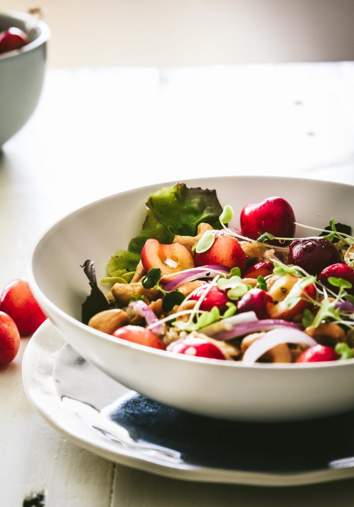 Quinoa salad topped with bright red cherries