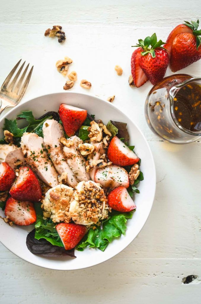 Green salad topped with grilled chicken, strawberries and baked goat cheese rounds