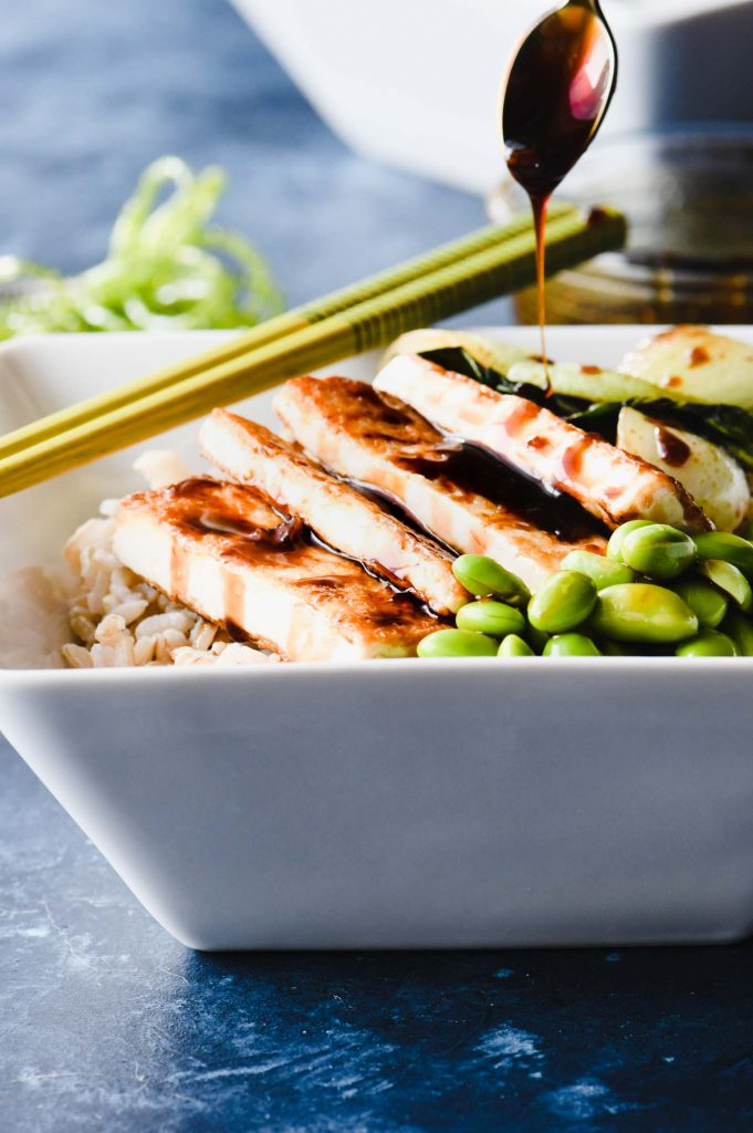 Tofu rice bowl on a bright blue background with green chopsticks